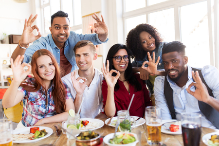 alright: happy friends showing ok hand sign at restaurant
