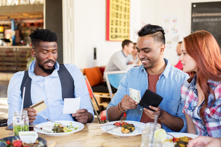 happy friends paying bill for food at restaurant Stock Photo