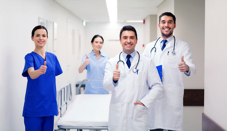 clinic, profession, people, health care and medicine concept - group of happy medics or doctors with gurney showing thumbs up at hospital corridor Stock Photo