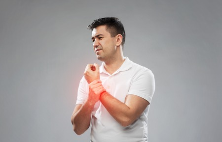 people, healthcare and problem concept - unhappy man suffering from pain in hand over gray background Stock Photo