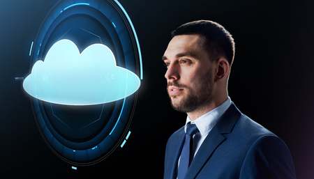 business, people and cloud computing concept - businessman in suit with virtual projection over black background
