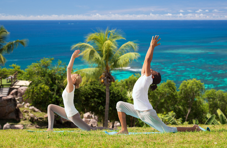fitness, sport, relax and people concept - couple making yoga in low lunge pose over natural background
