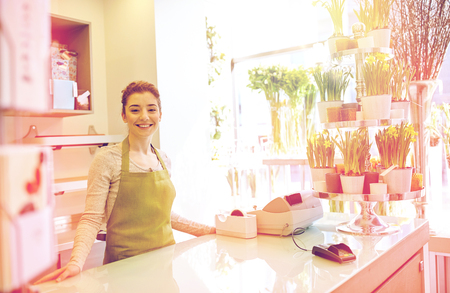 happy smiling florist woman at flower shop counter