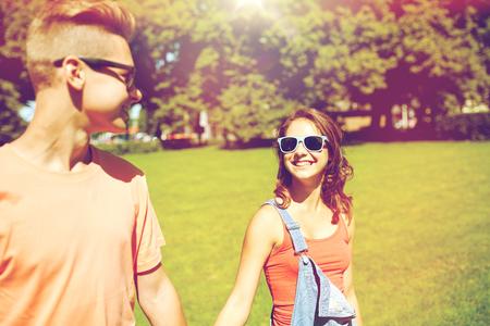 happy teenage couple walking at summer park Imagens - 82812189
