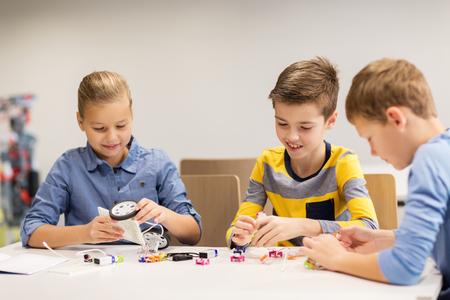 gelukkige kinderen het bouwen van robots op de school robotica Stockfoto