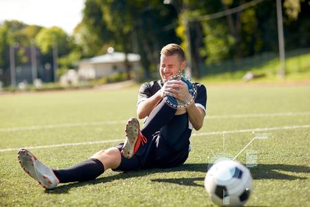 injured soccer player with ball on football field Reklamní fotografie