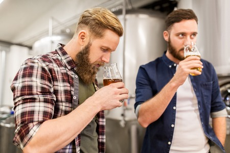 men drinking and testing craft beer at brewery Stock Photo