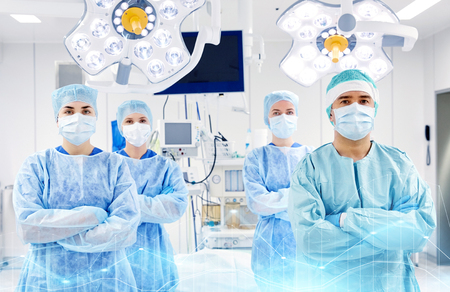 theatre masks: group of surgeons in operating room at hospital Stock Photo
