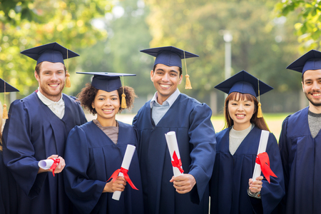 african student: happy students in mortar boards with diplomas