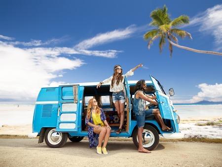 happy hippie friends in minivan car on beach Foto de archivo