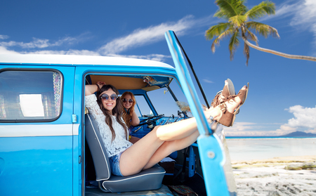 happy hippie women in minivan car on summer beach