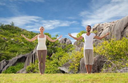 happy couple making yoga exercises on beach Stock Photo