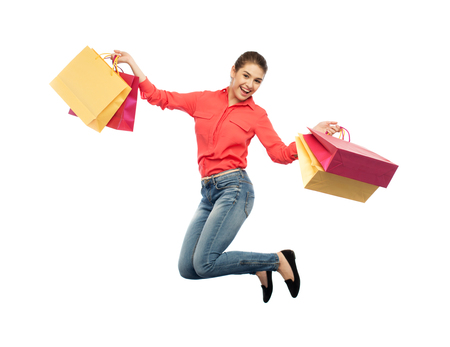 smiling young woman with shopping bags jumping Stock Photo