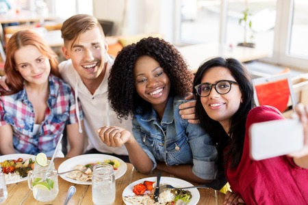 friends eating and taking selfie at restaurant Stock Photo