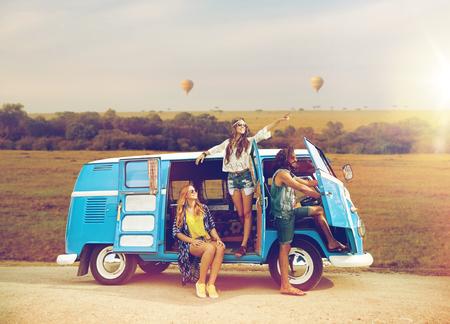 happy hippie friends in minivan car in africa