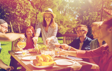 愉快的朋友吃晚餐在夏天庭院党