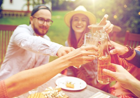 holiday gathering: happy friends with drinks at summer garden party