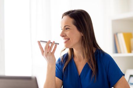 Vrouw met behulp van voice recorder op smartphone op kantoor Stockfoto - 82915512