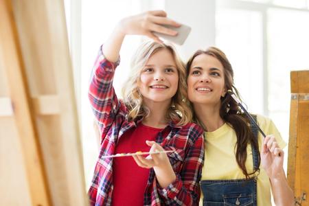 Kunstenaarsmeisjes nemen zelfie op kunststudio of school