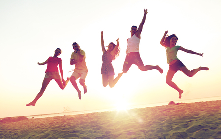 groovy: smiling friends dancing and jumping on beach