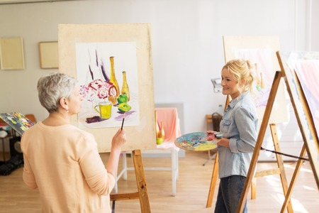 Artist women with easels painting at art school