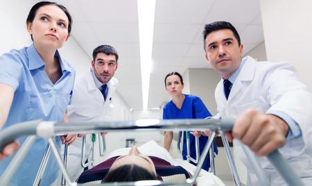medics with woman on hospital gurney at emergency