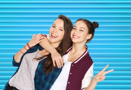 happy teenage girls hugging and showing peace sign photo