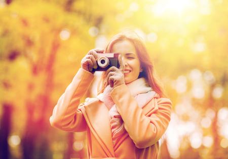 秋の公園でカメラで撮影する女性 写真素材