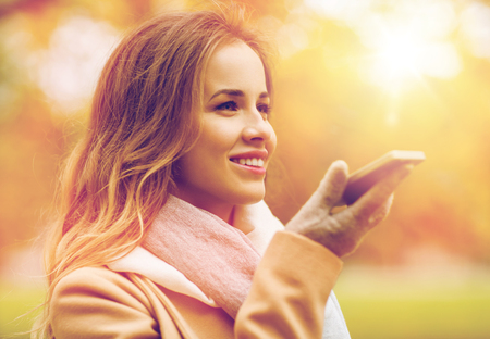 woman recording voice on smartphone in autumn park Stock Photo