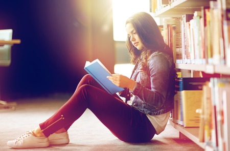 high school student girl reading book at library 스톡 콘텐츠