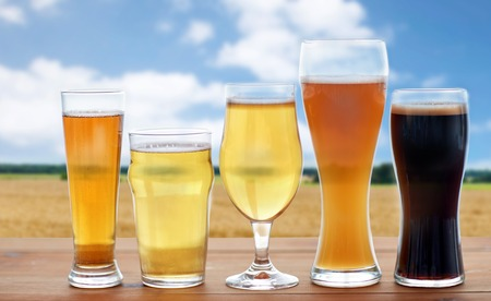 different types of beer glasses over cereal field