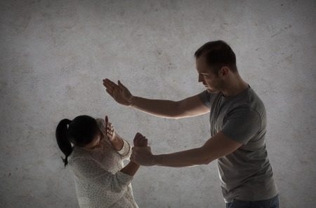 couple having fight and man beating woman Stock Photo