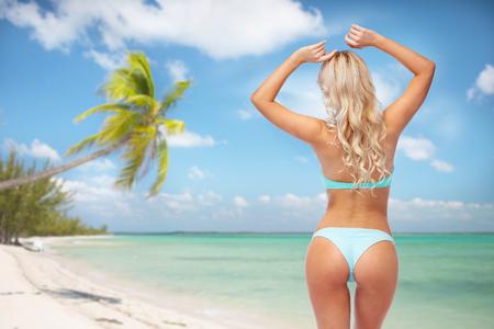 woman in bikini swimsuit from back on beach