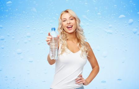 水のボトルと幸せな美しい若い女