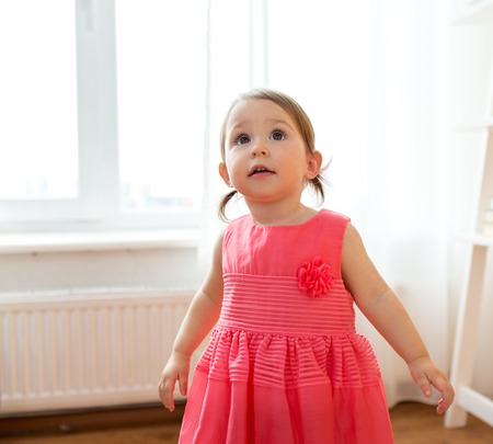 happy baby girl in dress at home