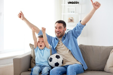 father and son watching soccer on tv at home Foto de archivo