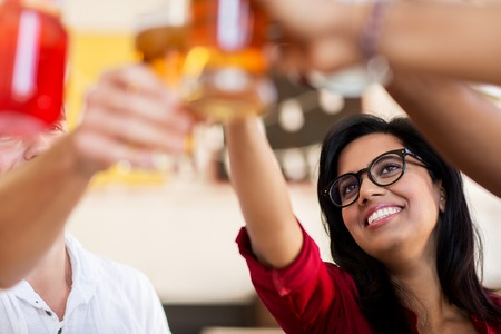 friends clinking glasses with drinks at restaurant