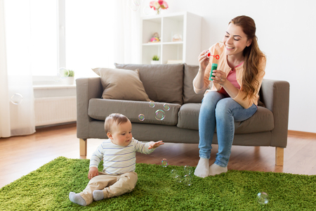 mother with soap bubbles playing with baby at home Stock Photo