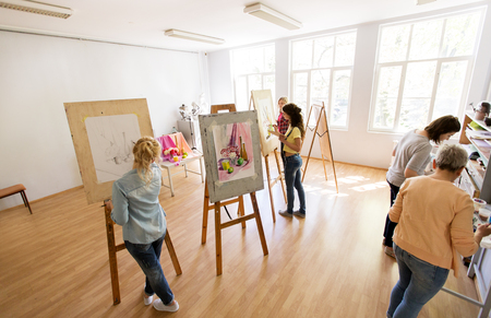 woman artists with brushes painting at art school Stock Photo