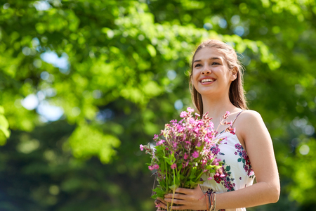 happy young woman with flowers in summer park Stock Photo