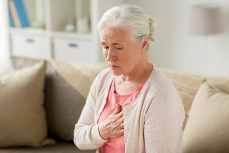 senior woman suffering from heartache at home Imagens