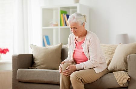 Mujer mayor que sufre de dolor en la pierna en casa Foto de archivo - 83697109