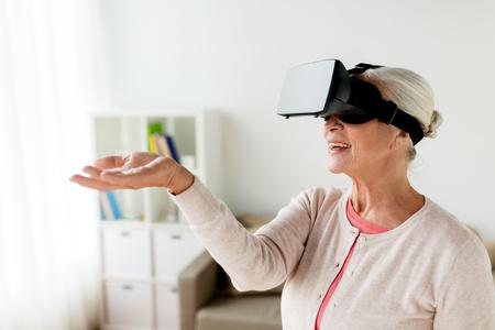 Tecnología, realidad aumentada, entretenimiento y concepto de la gente - mujer mayor con auriculares virtuales o gafas 3d jugando videojuegos en casa Foto de archivo - 83500312
