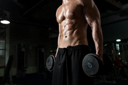 Cerca del hombre con pesas haciendo ejercicio en el gimnasio Foto de archivo - 83697112