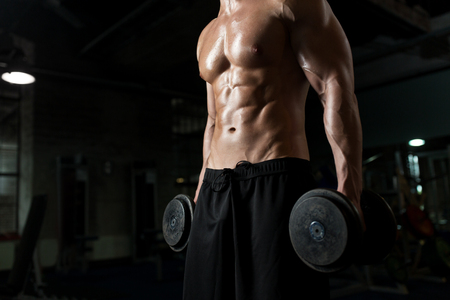 close up of man with dumbbells exercising in gym Stock Photo - 83697112
