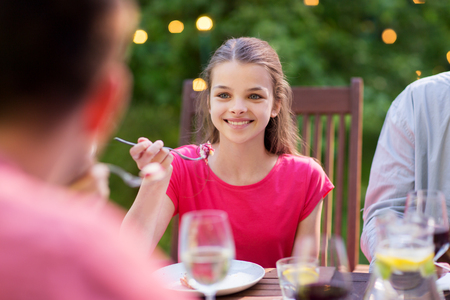 leisure, holidays and people concept - happy girl eating with family at festive dinner or summer garden party Stock Photo