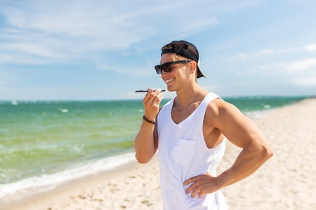 summer holidays and people concept - happy smiling young man in sunglasses using voice command recorder on smartphone on beach Stock Photo