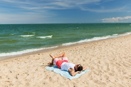 happy smiling young man sunbathing on beach towel