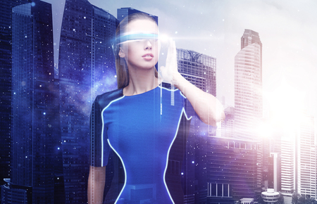woman in virtual reality glasses over space city photo