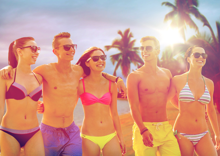 smiling friends in sunglasses on summer beach photo